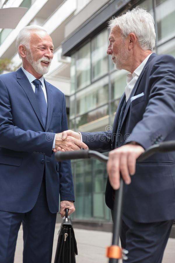 Two happy senior businessmen shaking hands, standing in front of an office building. Two happy senior gray-haired businessmen shaking hands, standing in front of royalty free stock image
