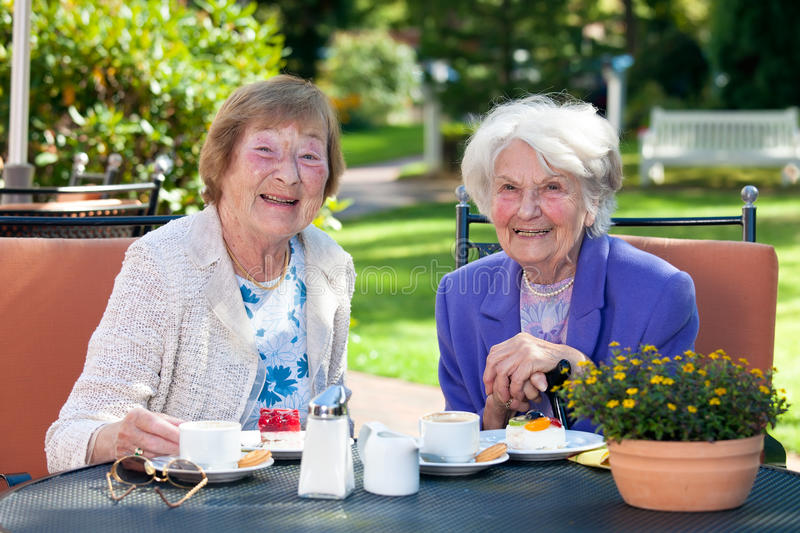 Two Happy Senior Ladies Having Snacks Outside. Close up Two Happy Senior Ladies Sitting at the Garden Table with Snacks While Looking at the Camera stock photo