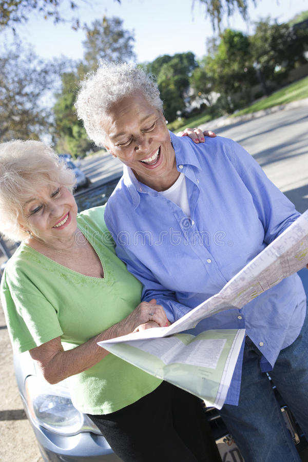 Two Happy Senior Women Reading Map. Happy senior women holding roadmap with friend standing besides royalty free stock photos