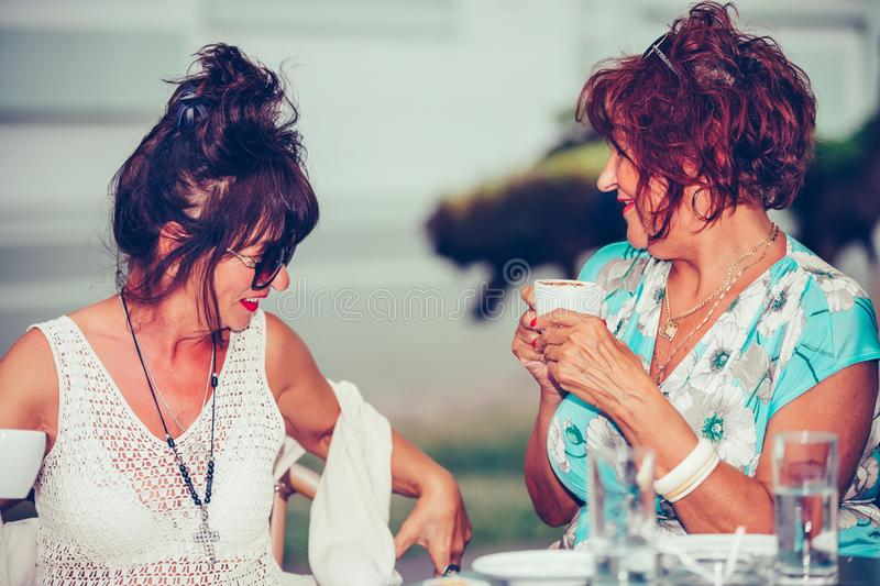 Two happy senior women talking and enjoying coffee together in a in cafe stock images