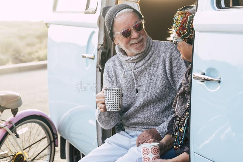 Two happy seniors and mature married couple travelling together the worls with a blue and white van - sitting on the van with a. Cup of coffee or tea - elderly royalty free stock photography