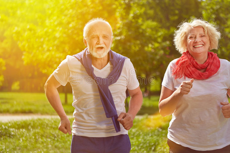 Two happy seniors running in nature stock images