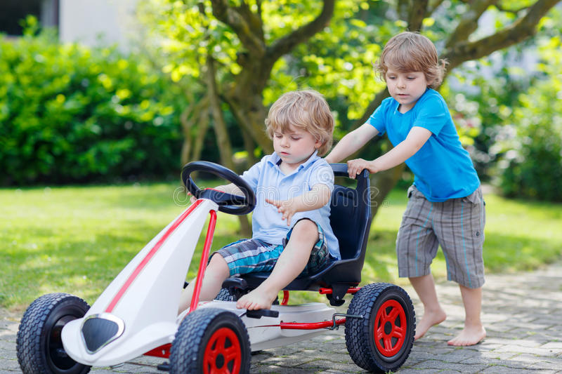 Two happy sibling boys having fun with toy car royalty free stock photos