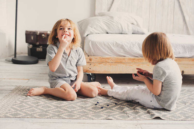 Two happy sibling boys playing together at home with toy cars royalty free stock photos