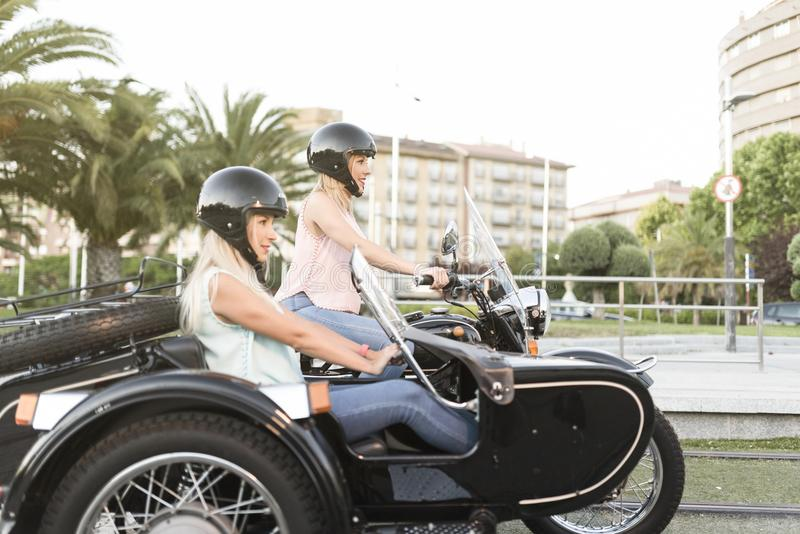 Two happy sister blonde women on sidecar bike smiling and happy stock image