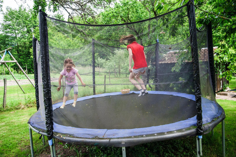 Two happy sisters on trampoline stock photography