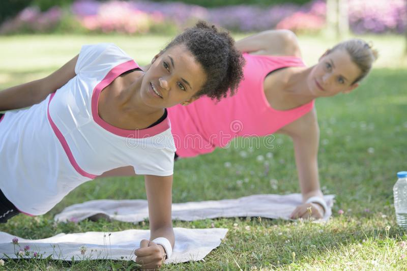 Two happy smiling fit young beautiful doing side plank royalty free stock images