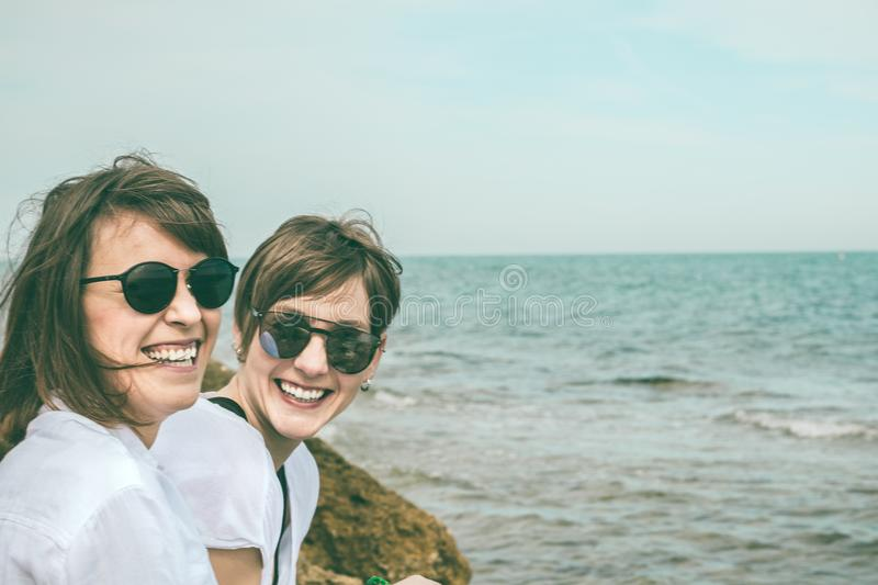 Two happy, smiling girls on the beach. Sensation of joy between two friends royalty free stock photography