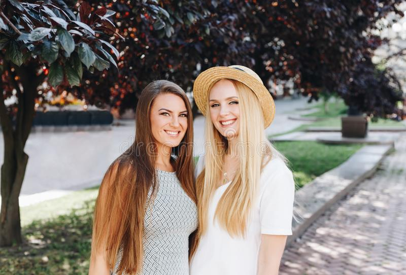 Two happy smiling girls are walking in the sunny city. Beautiful blonde and brunette walking down the street, students, travelers royalty free stock photography
