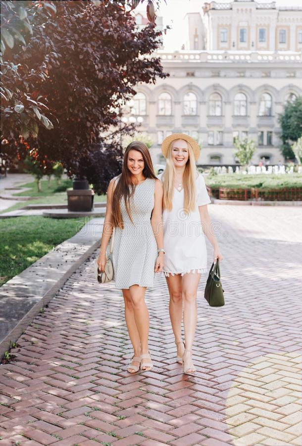 Two happy smiling girls are walking in the sunny city. Beautiful blonde and brunette walking down the street, students, travelers stock photo