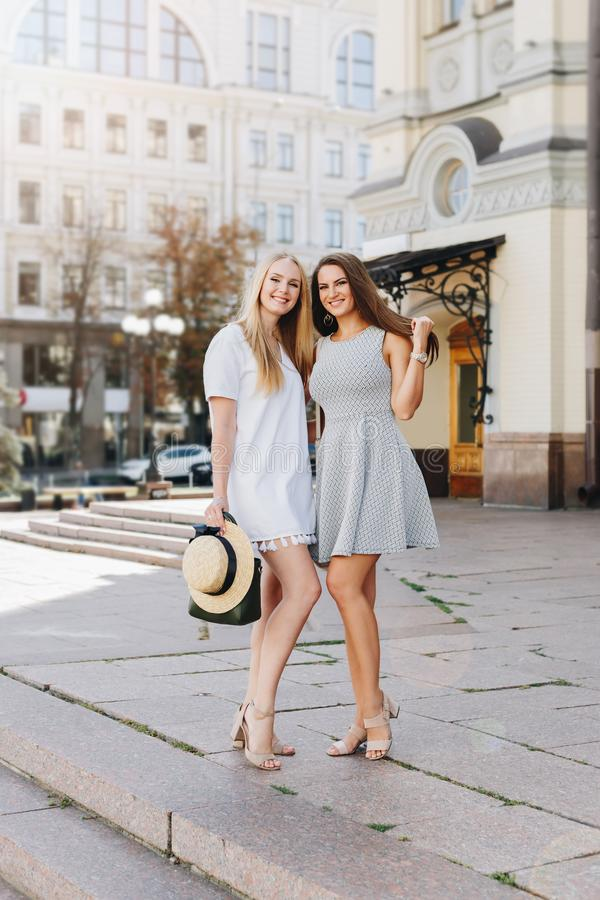 Two happy smiling girls are walking in the sunny city. Beautiful blonde and brunette walking down the street, students, travelers royalty free stock image