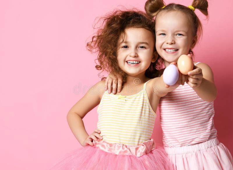 Two happy smiling kids girls demonstrate painted eggs on Easter day stock image