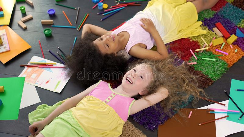 Two happy smiling multiracial girls lying on the floor, enjoying time together royalty free stock image