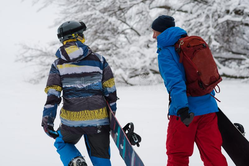 Two happy snowboarders is walking, talking and laughing royalty free stock images