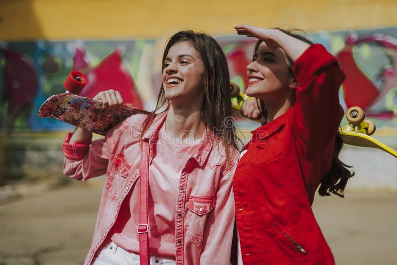 Two happy stylish hipster girls with skateboards. Urban lifestyle concept. Waist up portrait of young pretty happy hipster ladies staying with skateboards on stock images