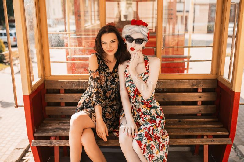 Two happy stylish lesbian girls with long hair in flower dress on background of train. Beautiful retro woman in black sunglasses. Two happy stylish lesbian girls stock images