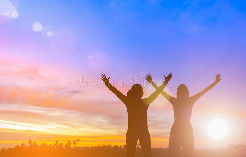 Two happy successful women raising arms toward beautiful scenery. People achieve life target goal. Business women raises hands as stock images