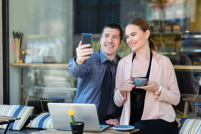 Two happy successful young business people smiling while taking selfie looking at mobile phone at cafe terrace stock images