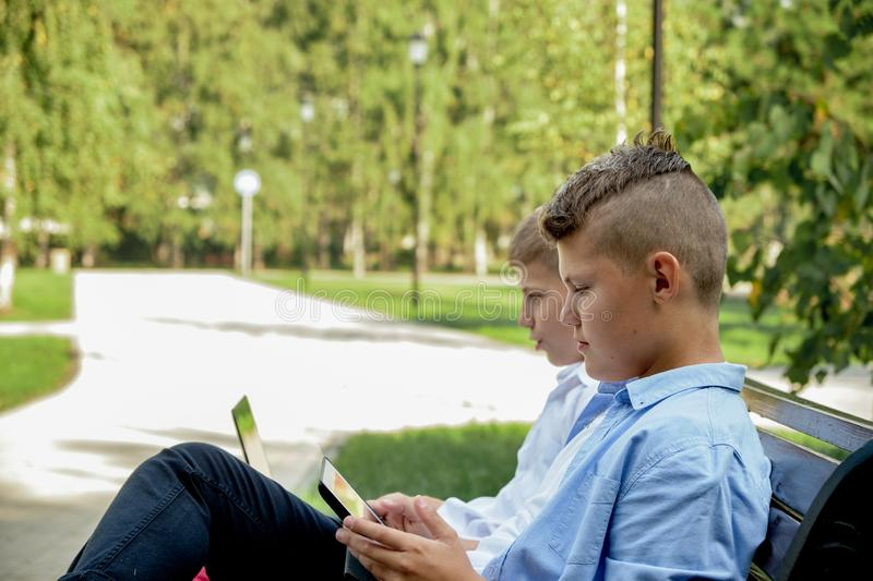 Two happy teenage friends using on mobile phone while relaxing in the park. Problems of modern youth, social networks royalty free stock images