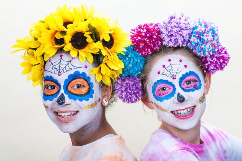 Two Teenage Girls in Dia de los Muertos Halloween Make Up. Two happy teenage teen girls in Dia de los Muertos Halloween make up royalty free stock images