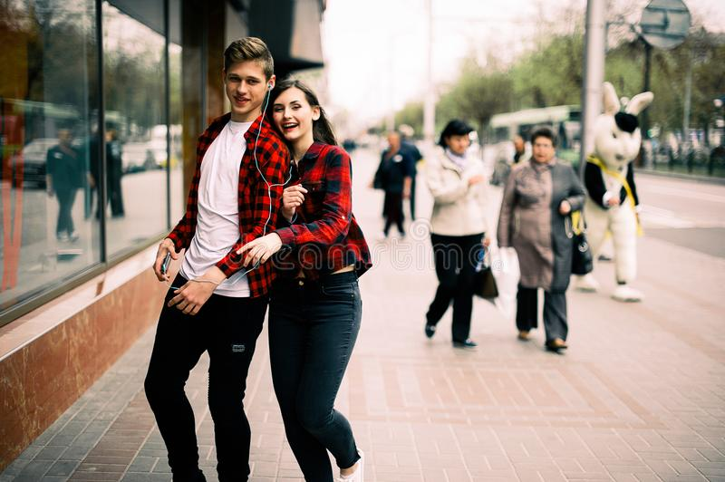 Two happy trendy teenage friends walking and dancing in the city, listening to the music with headphones, talking each other and s stock photos