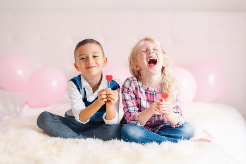 Two happy white Caucasian cute adorable funny children eating heart shaped lollipops stock image