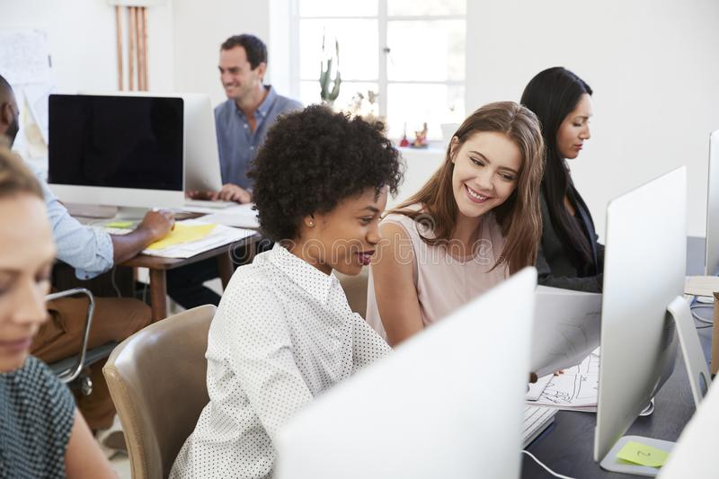 Two happy women discuss work at computer in open plan office royalty free stock image