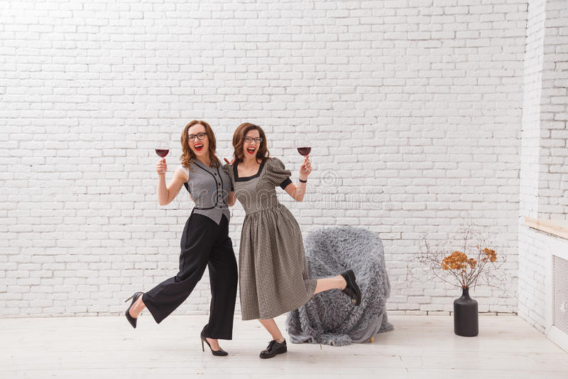 Two happy women, having fun and drinking red wine on party. Fashionable dressed with beautiful wavy hair. On loft white stock photo