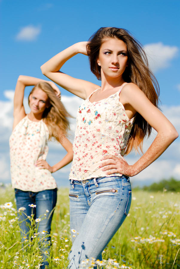Two happy women posing & enjoying sun outdoors stock photos