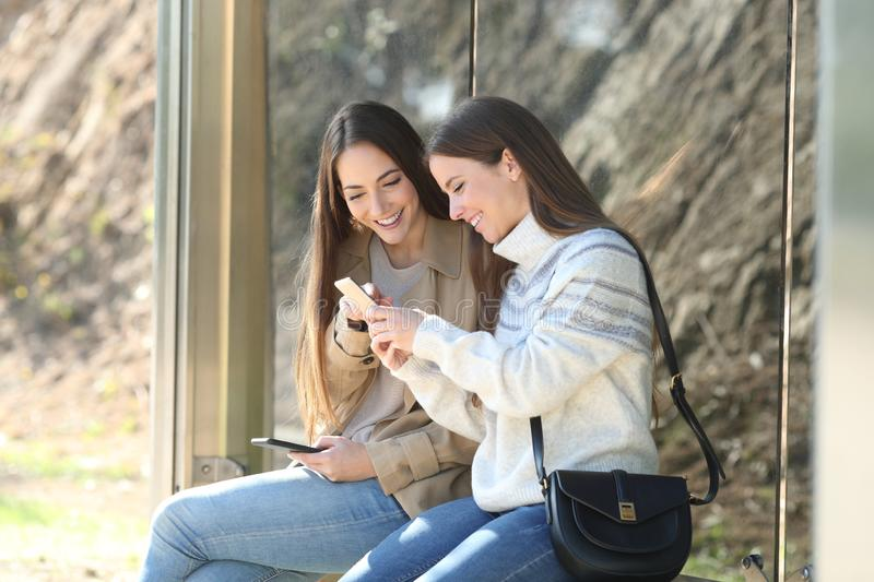Two happy women waiting in a bus stop checking phones stock photo