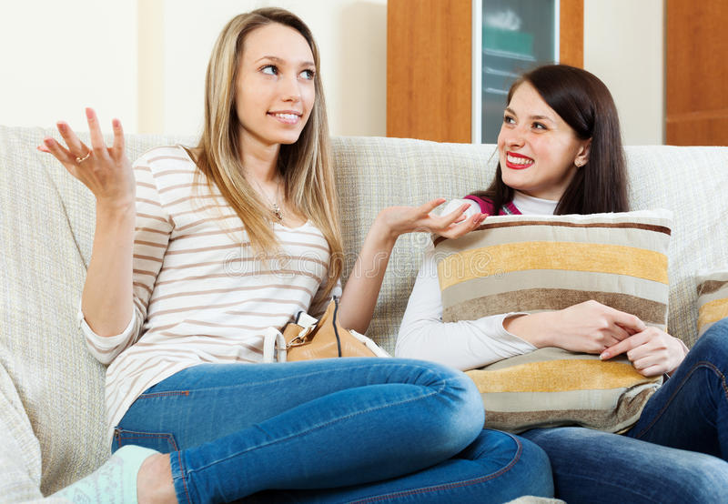 Two happy womnen gossiping on sofa