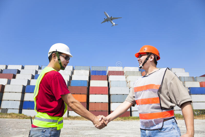 Two happy workers handshaking. Before transportation containers stock image