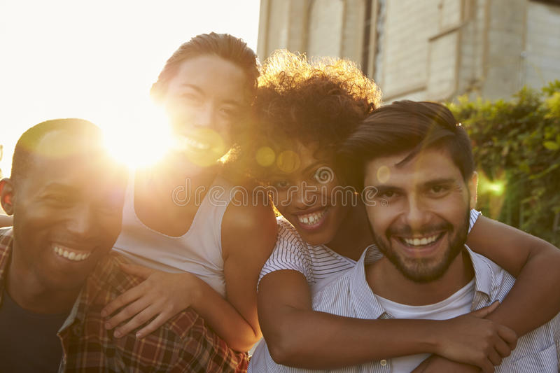 Two happy young adult couples piggybacking the street stock image