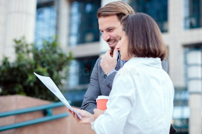 Two happy young business partners meeting in front of an office building, looking at sale charts and discussing project details. Two smiling happy young business stock image