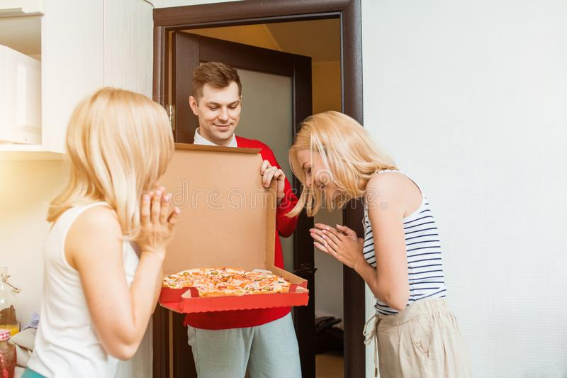 Two young caucasian woman receiving pizza from delivery man at home. Two happy young caucasian women receiving pizza from delivery men at home. Delivery men in royalty free stock photography