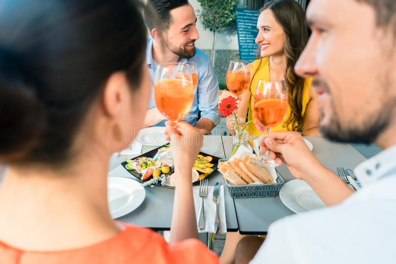 Two happy young couples toasting while sitting together at restaurant stock images