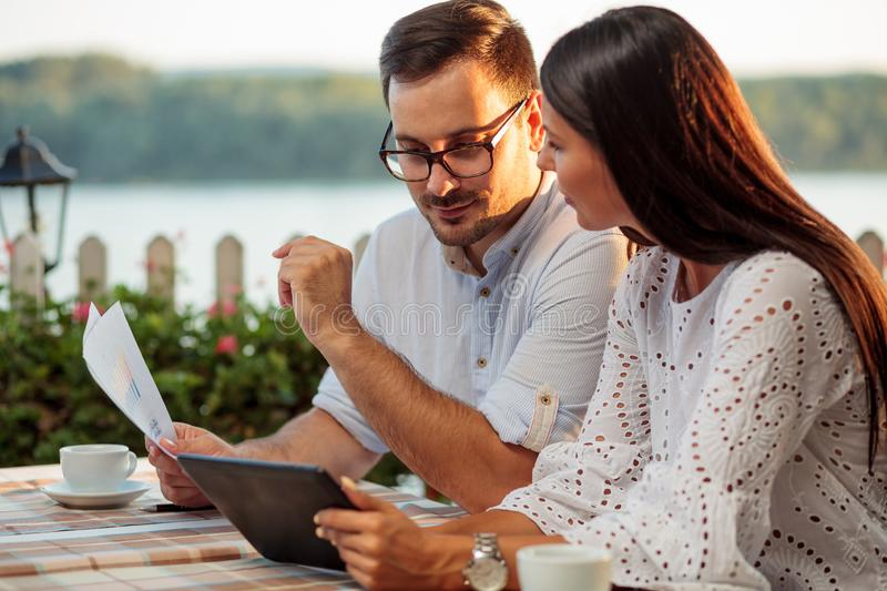 Two happy young freelancers working in a restaurant by the river stock photography