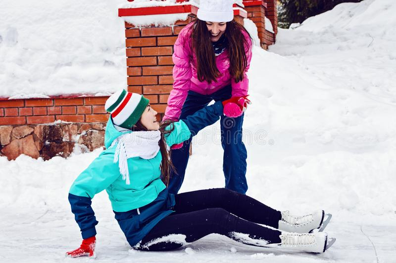 Two happy young girl ice skating in winter Park. It helps other to rise after a fall royalty free stock photos