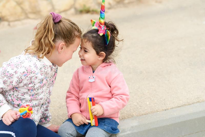 Two happy young girls in a city street. Toddler girl dressing up as a unicorn. royalty free stock photo
