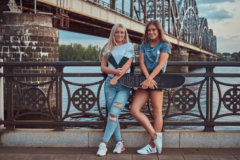 Two happy young hipster girls holds skateboard and leaning on a guardrail on a background of the old bridge. royalty free stock photography