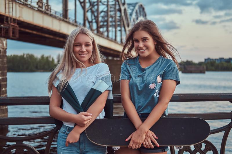 Two happy young hipster girls holds skateboard and leaning on a guardrail on a background of the old bridge. stock images