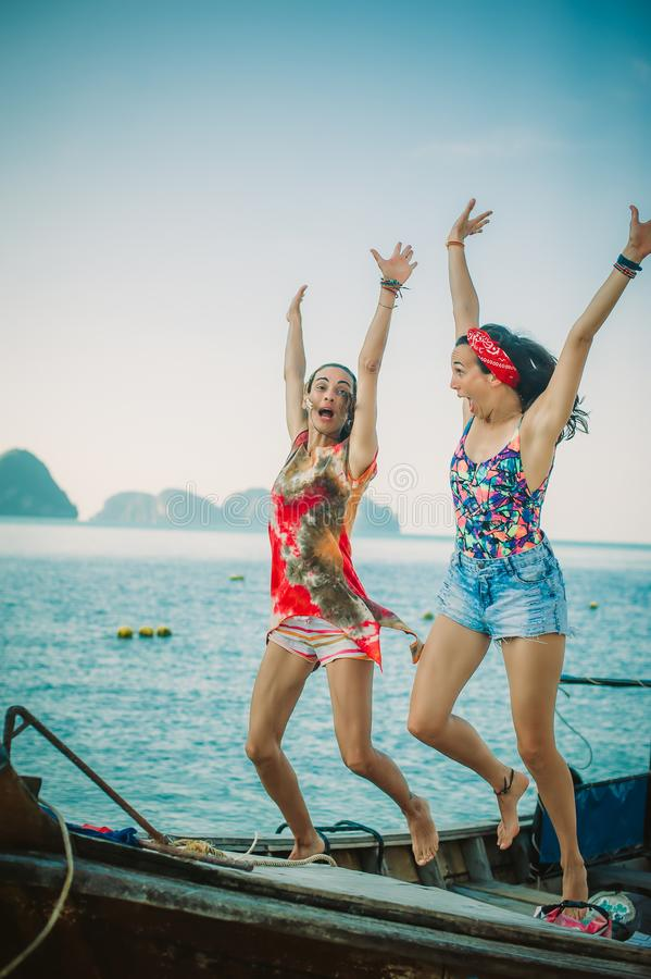 Two happy young woman jumping and laughing on the boat royalty free stock photos