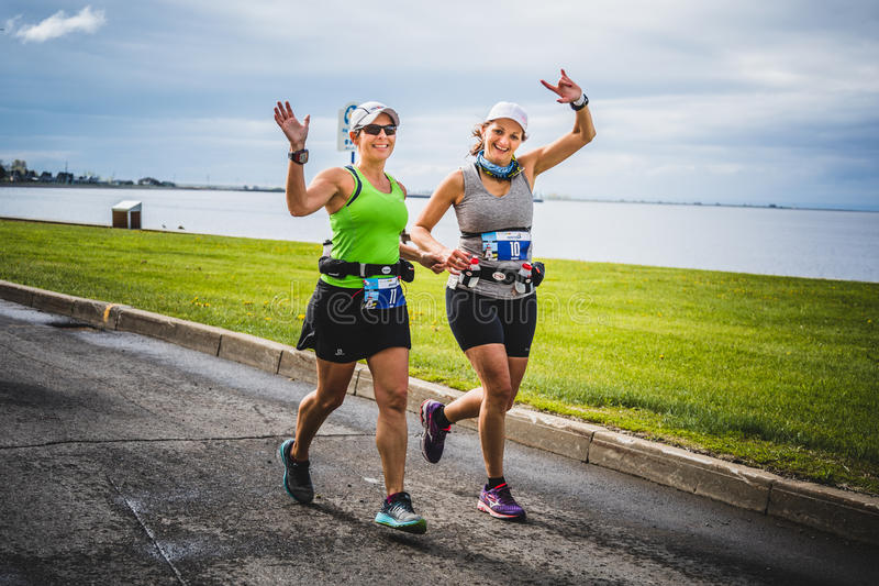 Two Happy Young Women on the first km of the Marathon. CARLETON, CANADA - June 4, 2017. During the 5th Marathon of Carleton in Quebec, Canada. Two Happy Young royalty free stock images