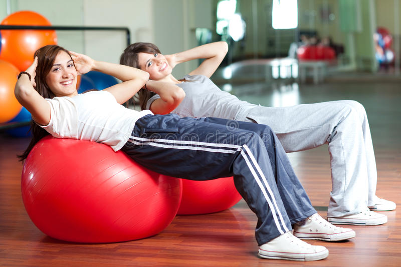 Two happy young women in the gym royalty free stock photos