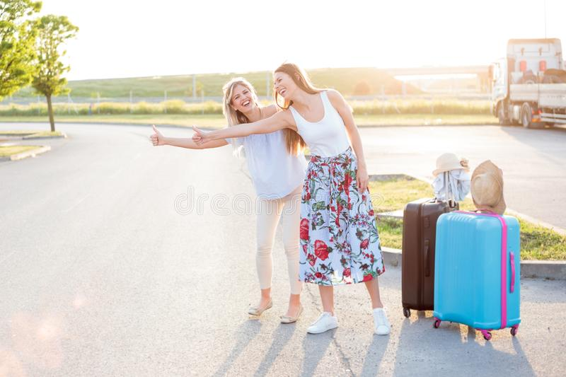 Two happy young women having a great time while hitchhiking royalty free stock photos
