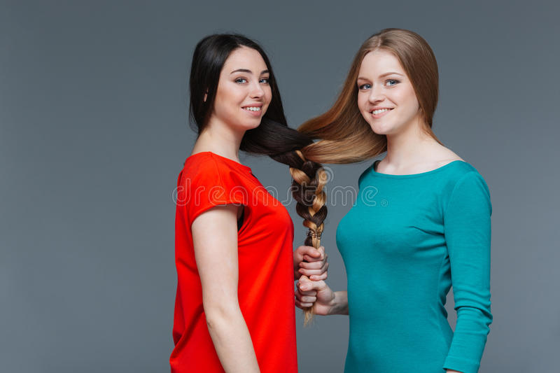 Two happy young women made one brair with their hair stock images