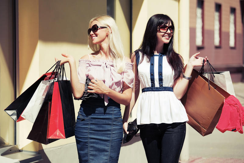 Two happy fashion women with shopping bags walking in street. Two happy young fashion women with shopping bags walking in city street stock images