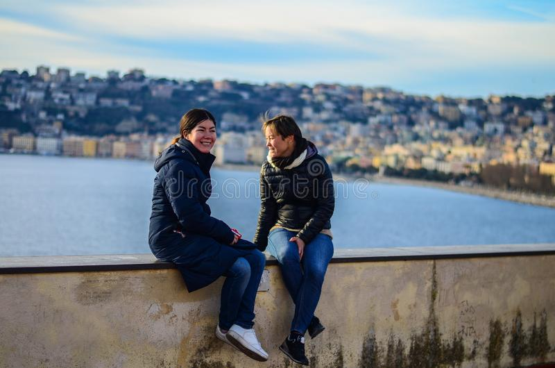 Two smiling girls sit near the sea. City in the background. Naples, Italy royalty free stock photos