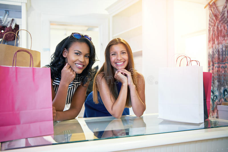 Two happy young women waiting to pay in a store royalty free stock photography