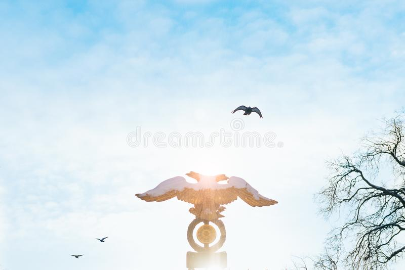 Two-headed eagle on sky background at sunrise with birds on the background. Russian emblem, golden double headed eagle royalty free stock photo